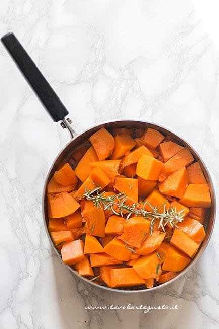 Aggiungere la zucca tagliata a pezzi - Ricetta Vellutata di zucca e carote
