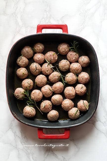 aggiungere in teglia le polpette e condirle - Ricetta Polpette di carne al forno