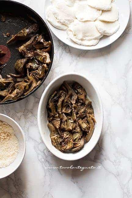 Assemblare la parmigiana di carciofi alternando provola e parmigiano