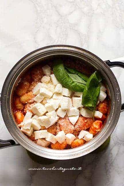 Mantecare in pentola gli gnocchi di patate con mozzarella, basilico e parmigiano - Ricetta gnocchi alla sorrentina