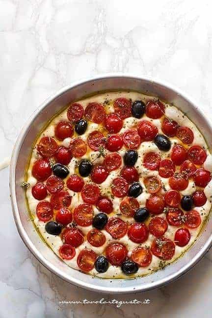 Condire la focaccia con pomodorini e olive nere - Ricetta Focaccia barese