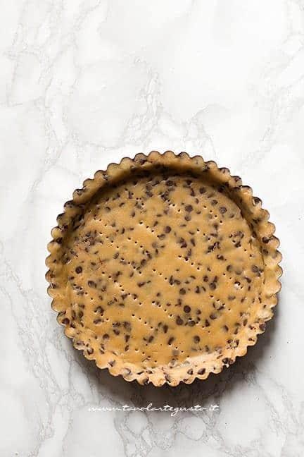 Foderare con la frolla cookie uno stampo per crostata - Ricetta Crostata cookies