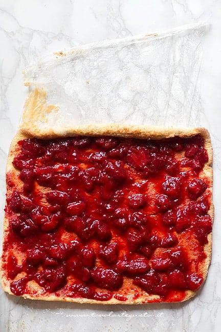 Spalmare uno strato di fragole sulla pasta biscotto - Ricetta Rotolo alle fragole