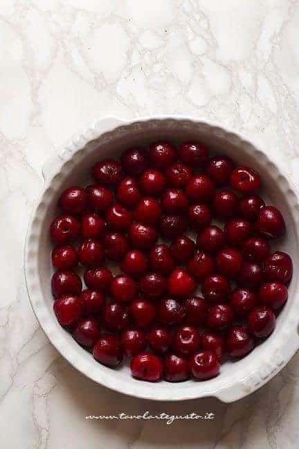 Aggiungere tutte le ciliegie in teglia - Ricetta Clafoutis di ciliegie