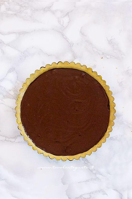 versare la crema di cioccolato nel guscio di frolla vegan - Ricetta Crostata vegana al cioccolato