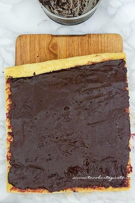 Aggiungere la ganache al cioccolato e arrotolare - Ricetta Tronchetto di Natale