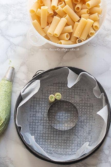 inserire i maccheroni in teglia - Ricetta Timballo di pasta