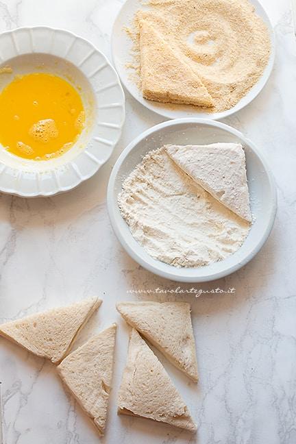impanare le fette di pane ripiene di mozzarella - Ricetta mozzarella in carrozza al forno
